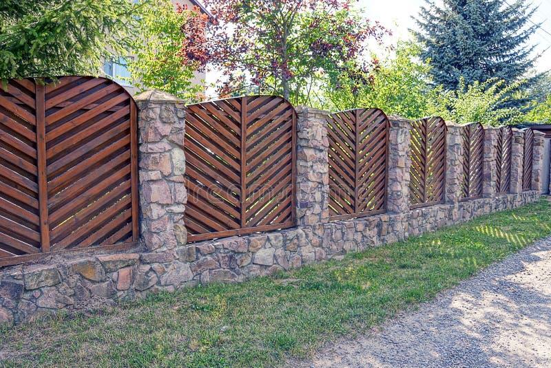 Cerca larga de la piedra de madera y marrón en la calle en la hierba foto de archivo