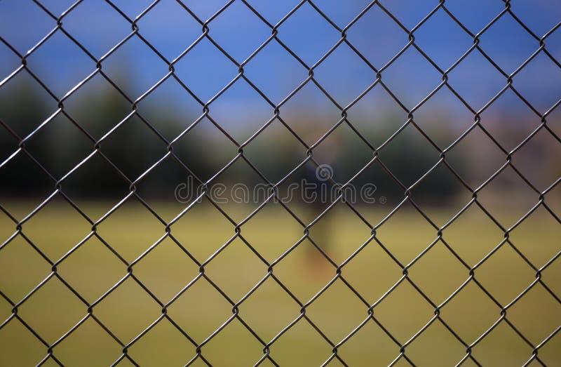 Cerca metálica de la malla del alambre alrededor de un campo de fútbol Fondo borroso, cierre encima de la visión con los detalles fotos de archivo libres de regalías