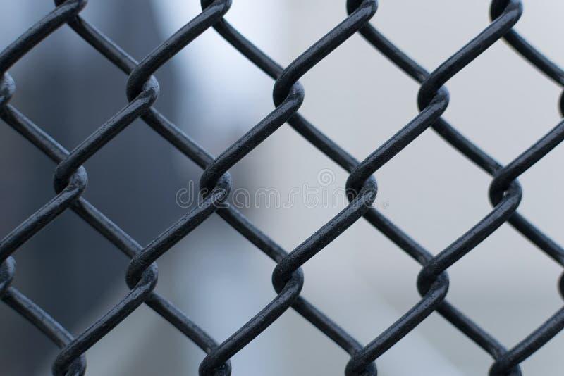 Cerca negra contra un fondo borroso liso de la salida, primer de la alambrada imágenes de archivo libres de regalías
