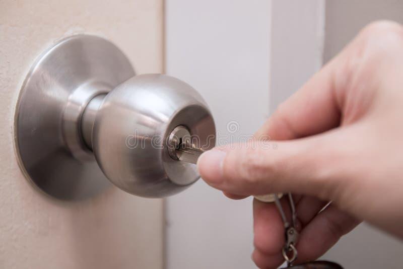 Cerca para arriba de la mano de la mujer usando la llave para desbloquear o cerrar la puerta blanca imagenes de archivo