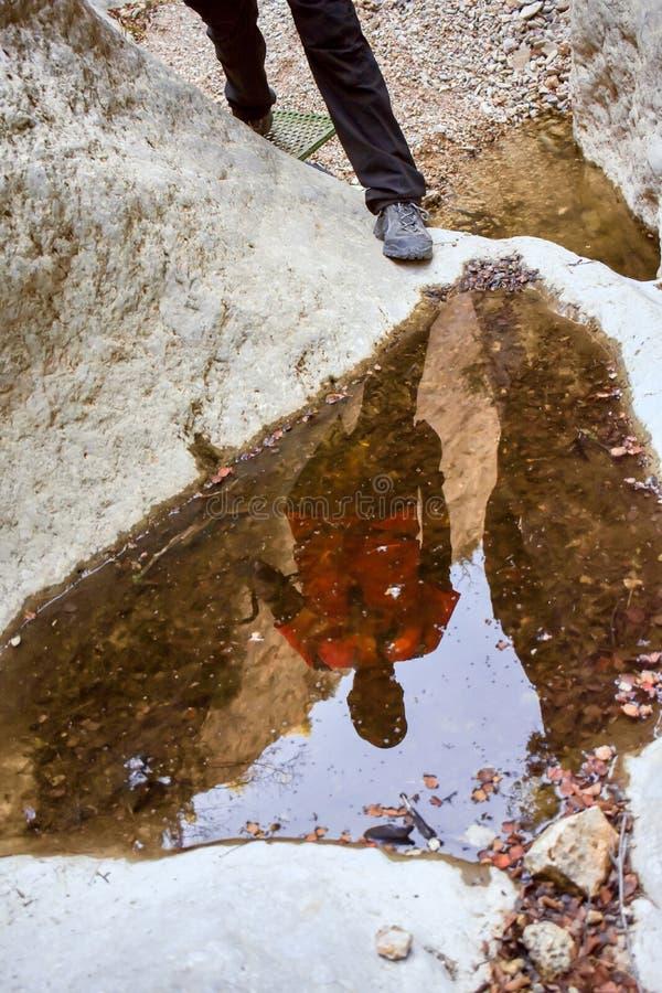 cerca para arriba de la reflexión en una paleta del agua de un caminante que hace un esfuerzo para subir el barranco en una monta imagen de archivo