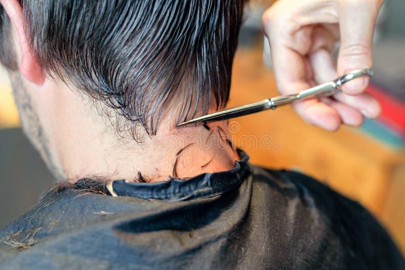 Cerca para arriba de las manos del peluquero que cortan el filamento del pelo del hombre Empleo profesional del peluquero o del p fotografía de archivo