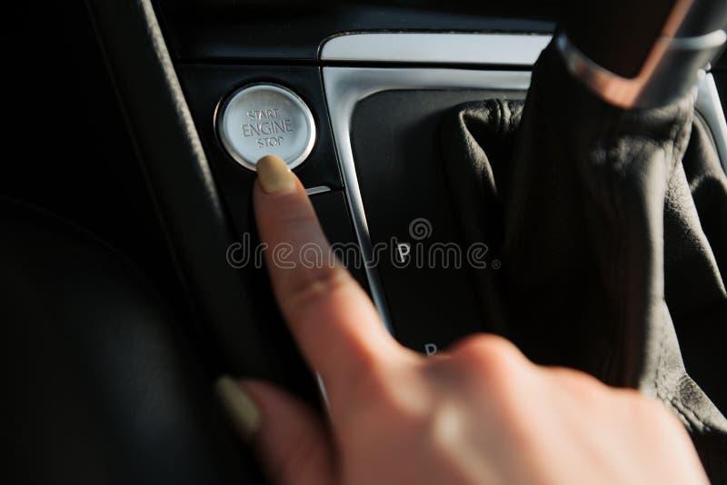 Cerca para arriba del finger de la mujer que presiona el botón partida/parada del motor en el coche imágenes de archivo libres de regalías
