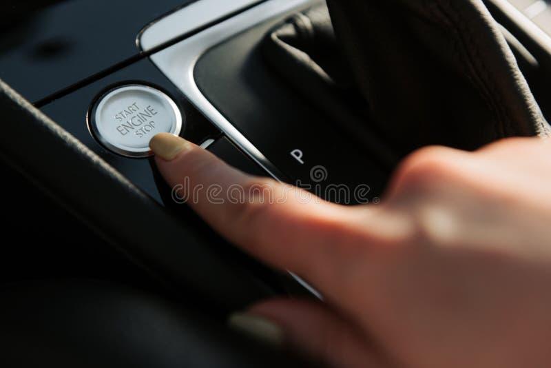 Cerca para arriba del finger de la mujer que presiona el bot?n partida/parada del motor en el coche fotos de archivo