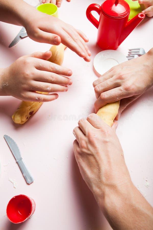 Cerca para arriba, la hija de la madre y del niño que prepara la pasta, cuece las galletas Las manos del niño que cuecen las gall imagen de archivo libre de regalías