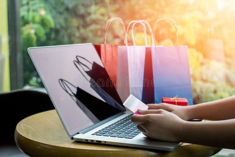 Cerca para arriba, teclado del ordenador portátil de la mujer que mecanografía asiática joven y sostener la tarjeta de crédito en fotografía de archivo libre de regalías