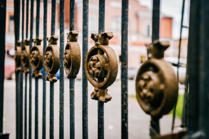Cerca preta forjada com o ornamento de bronze bonito imagem de stock royalty free
