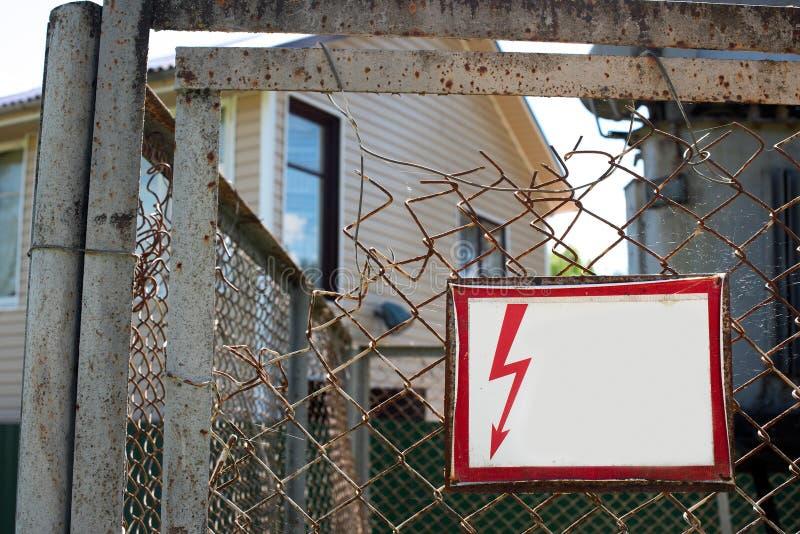 Cerca quebrada do metal com um sinal de perigo fotografia de stock