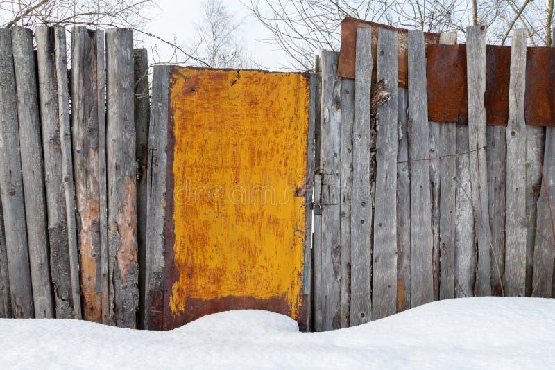 Cerca rústica de madeira cinzenta com porta oxidada foto de stock