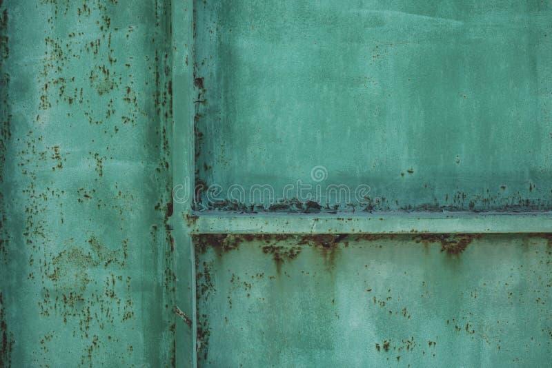 Cerca suja da folha do metal verde Placa do molde dos escapes do grunge da oxidação Pintura velha na cerca Arte abstrata de cobre fotografia de stock