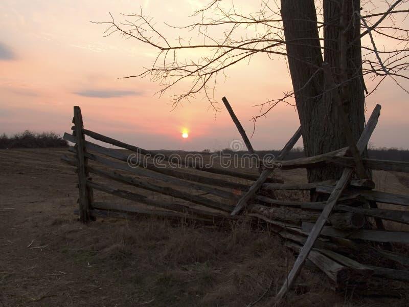 Cerca vieja en la puesta del sol imagenes de archivo