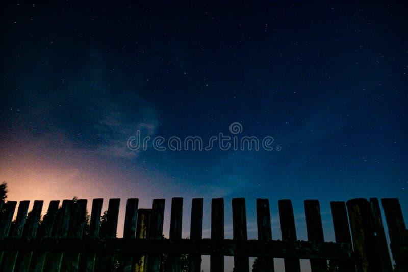 Cerca y cielo nocturno estrellado antes de la salida del sol fotografía de archivo