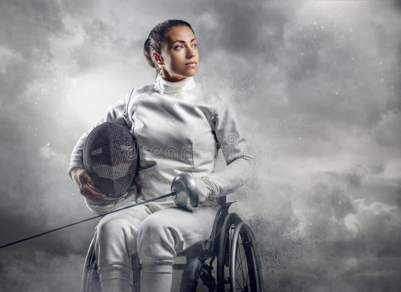 Cercador de sexo femenino en silla de ruedas con la máscara de la seguridad de una cara que sostiene el estoque imagen de archivo libre de regalías
