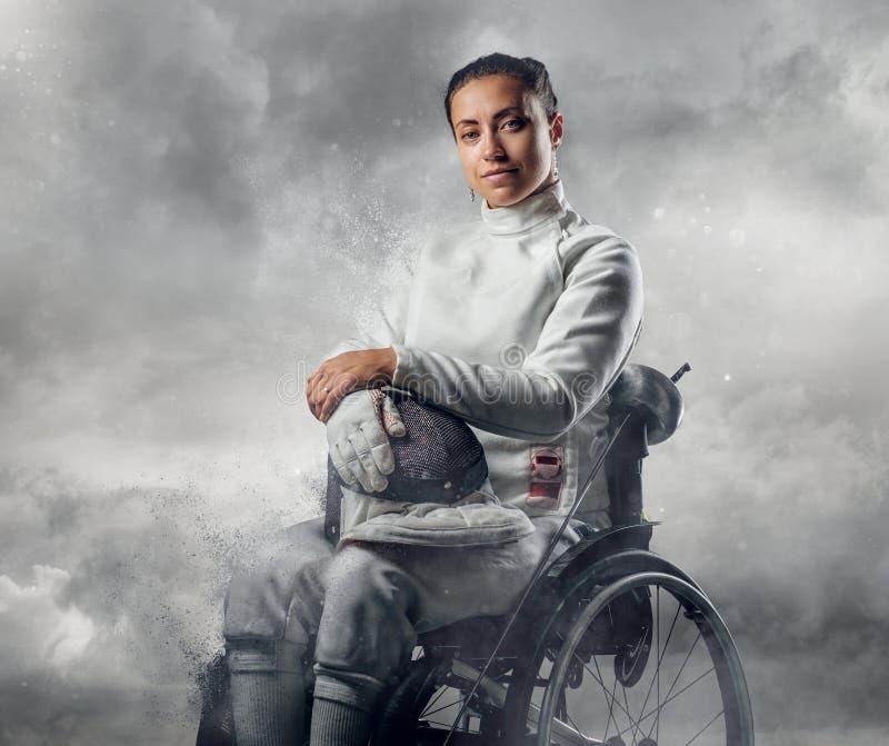 Cercador de sexo femenino en silla de ruedas con la máscara de la seguridad de una cara que sostiene el estoque fotos de archivo
