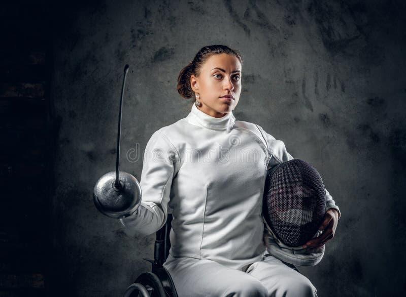Cercador de sexo femenino en silla de ruedas con la máscara y el estoque de la seguridad imágenes de archivo libres de regalías