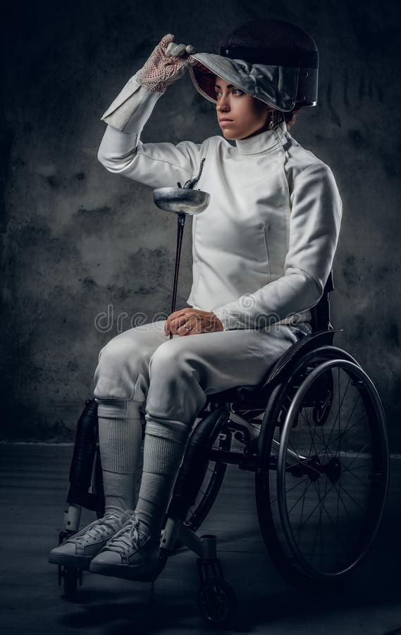 Cercador de sexo femenino en silla de ruedas con la máscara y el estoque de la seguridad imagen de archivo