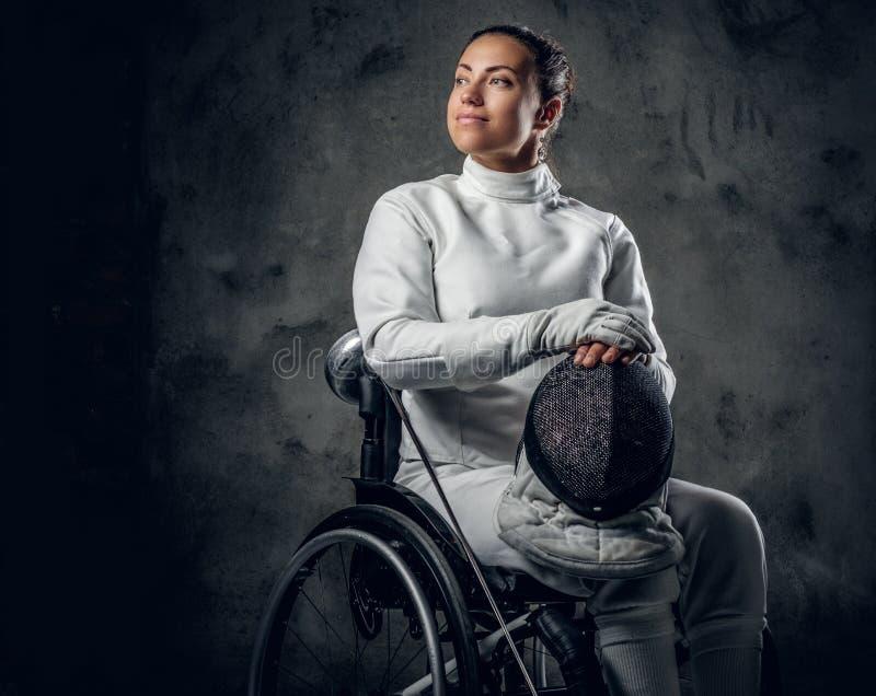Cercador de sexo femenino en silla de ruedas con la máscara y el estoque de la seguridad fotografía de archivo libre de regalías