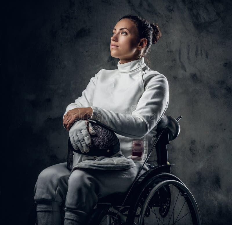 Cercador de sexo femenino en silla de ruedas con la máscara y el estoque de la seguridad fotografía de archivo