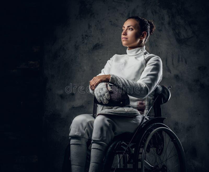 Cercador de sexo femenino en silla de ruedas con la máscara y el estoque de la seguridad fotos de archivo
