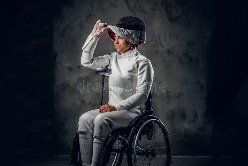 Cercador de sexo femenino en silla de ruedas con la máscara y el estoque de la seguridad imagenes de archivo