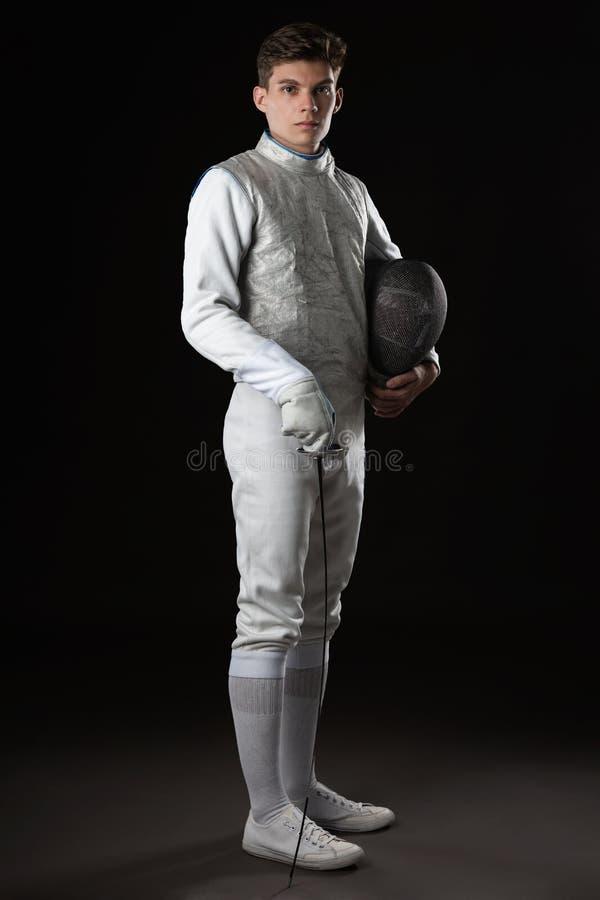 Cercador de sexo masculino joven hermoso en el traje de cercado blanco fotografía de archivo libre de regalías