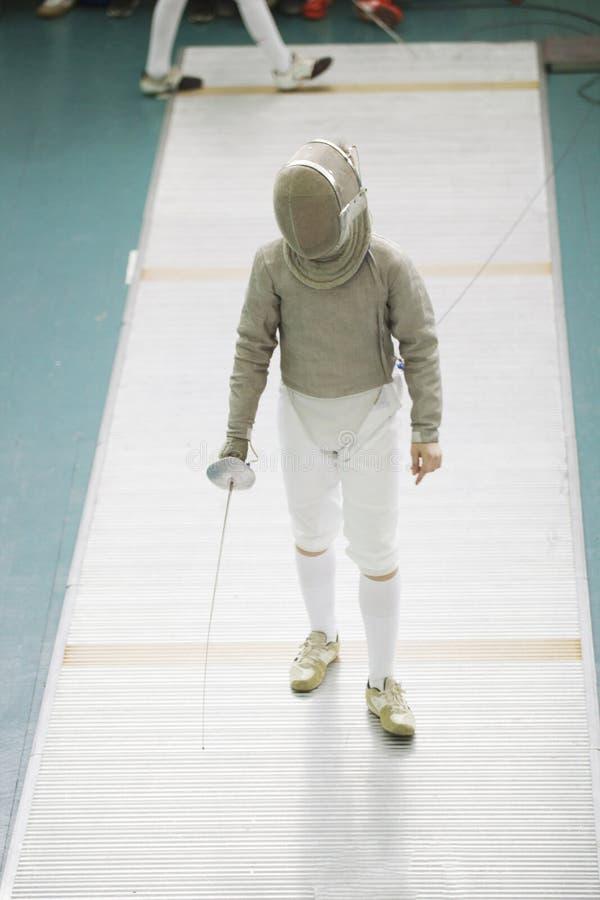 Cercador del adolescente del muchacho en traje especial en la competencia de cercado con el estoque imagen de archivo