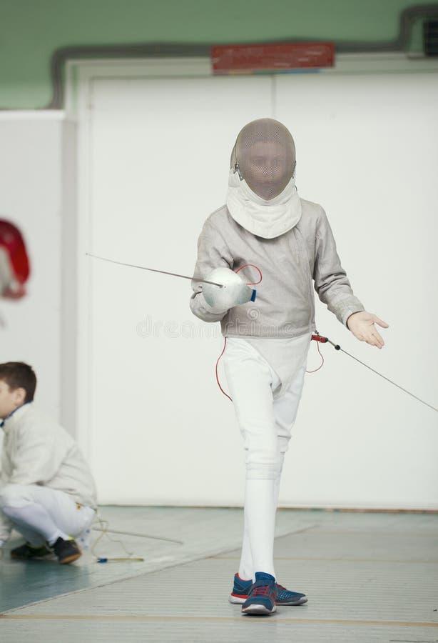 Cercador del adolescente del muchacho en traje especial en la competencia de cercado con el estoque en la posición que lucha fotos de archivo