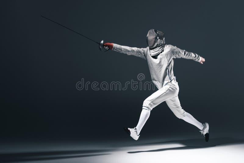 Cercador en máscara de cercado con el estoque que salta en gris imagen de archivo libre de regalías