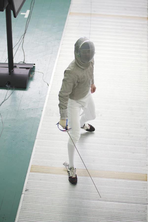 Cercador joven del adolescente en traje especial en la competencia de cercado con el estoque foto de archivo libre de regalías