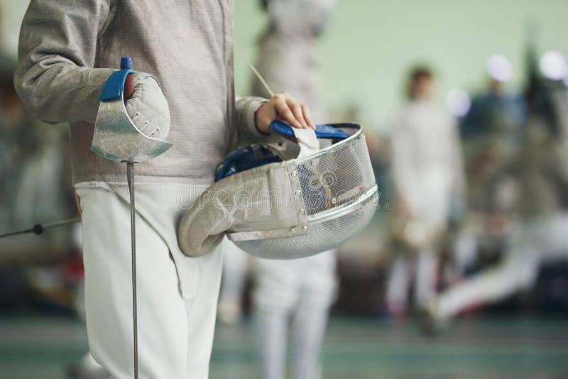 Cercador joven que lleva a cabo la hoja y la máscara protectora en su mano en el torneo de cercado fotografía de archivo libre de regalías