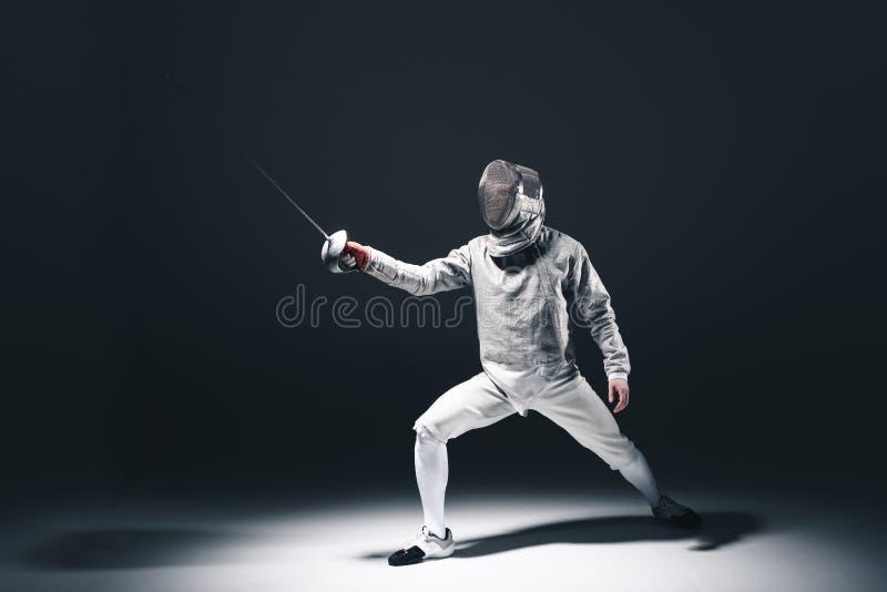 Cercador profesional en máscara de cercado con el estoque que se coloca en la posición imagenes de archivo
