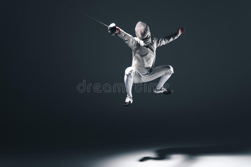 Cercador profesional en máscara de cercado con el salto del estoque foto de archivo libre de regalías