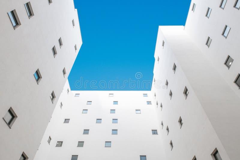 Cercando il cortile della costruzione di appartamento - facciata, corte e cielo blu di costruzione immagine stock