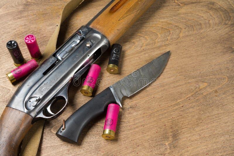 Cercando il fucile e le munizioni trovi su fondo di legno Copi lo spazio fotografia stock
