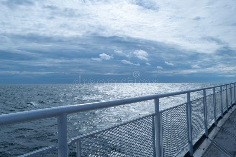 Cercando no andar superior de um navio, convirgindo com o horizonte e o céu azul impressionante na distância fotografia de stock