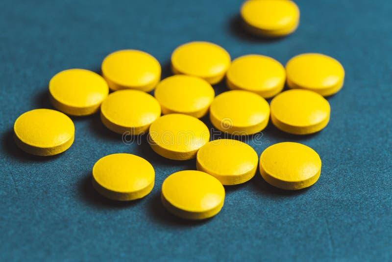 cercano para arriba de píldoras amarillas en un fondo azul fotos de archivo