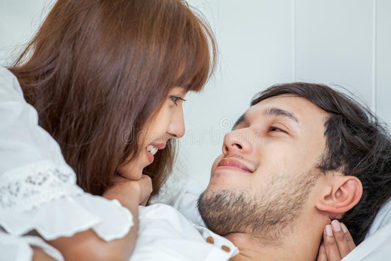 cercano para arriba de pares felices asiáticos jovenes en el amor que miente junto en cama sueño Relájese romántico imagen de archivo