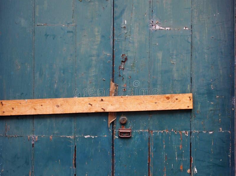 cercano para arriba de una puerta de madera pintada verde de peladura vieja del tabl?n obstruida cerrada con un pedazo de madera  imagen de archivo libre de regalías