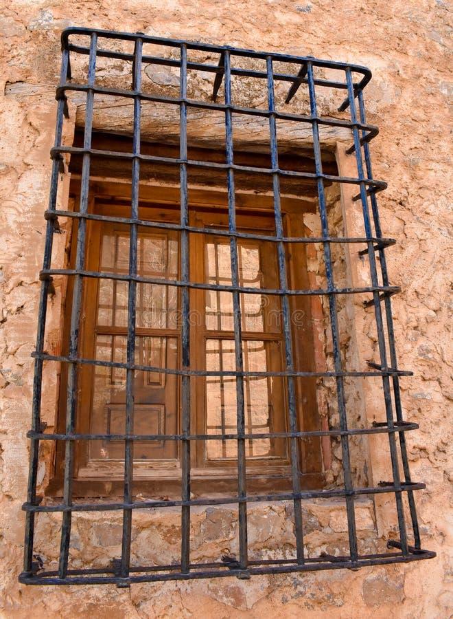 cercano para arriba de una ventana de madera vieja con las barras del hierro que bloquean el acceso, en una pared del hormigón y  imagen de archivo