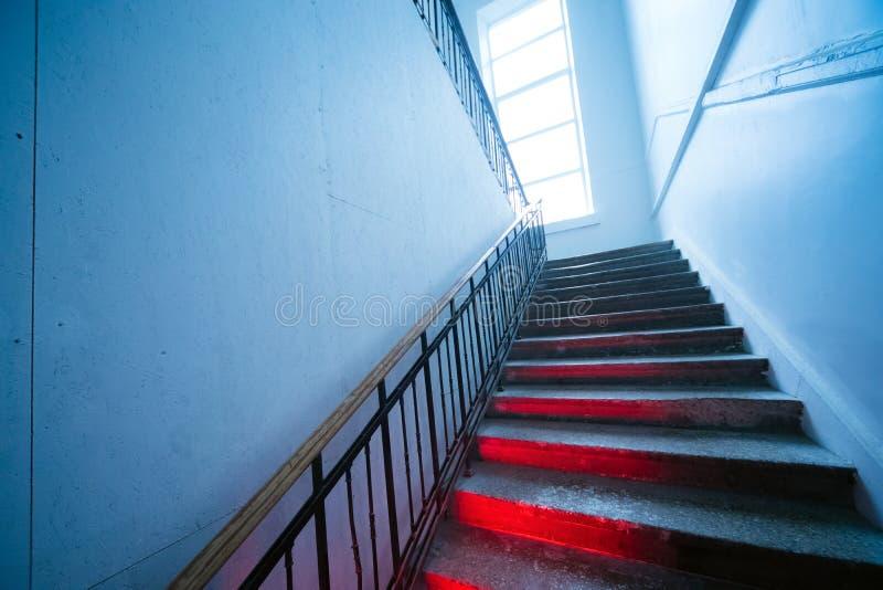 Cercare le scala distorte spaventose Scale che vanno su con la luce rossa sui punti immagini stock libere da diritti
