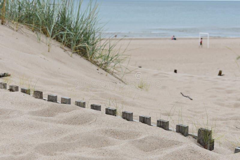 Cercas de madera enterradas debajo de la arena blanca imagen de archivo