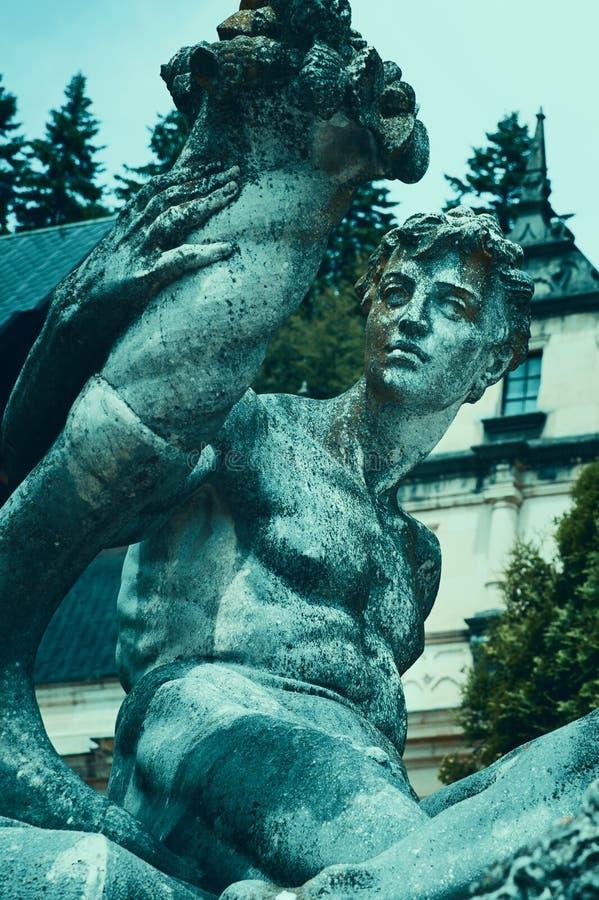 A cerceta cobre o efeito na fonte decorativa com as estátuas na frente do castelo de Peles, Sinaia, Romênia foto de stock