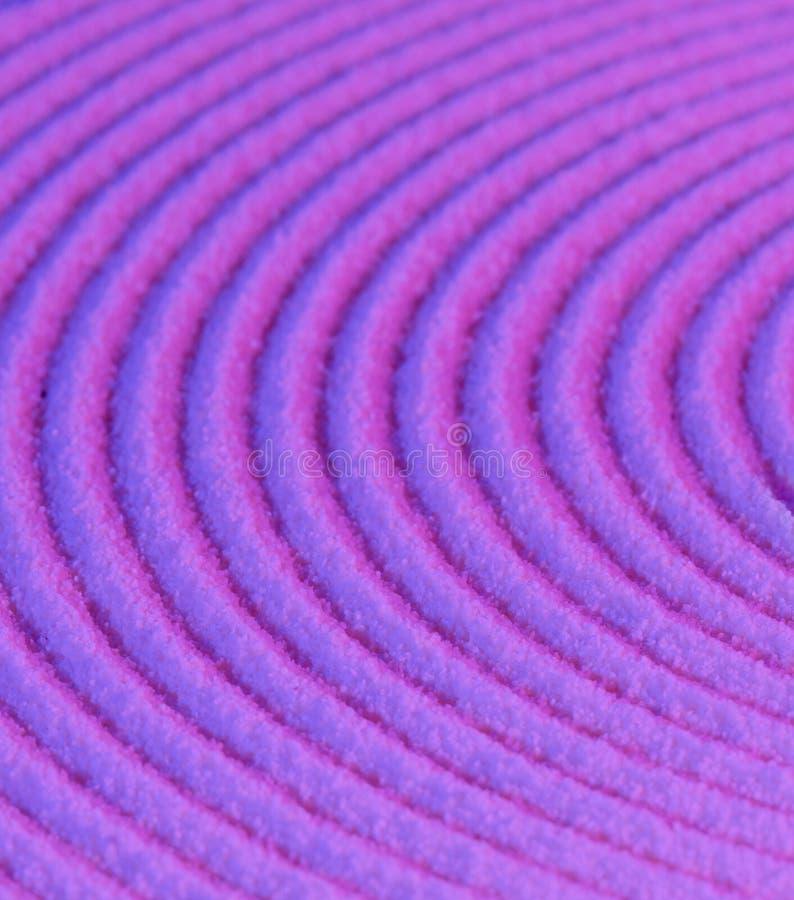 Cerchi concentrici sulla sabbia viola fotografia stock