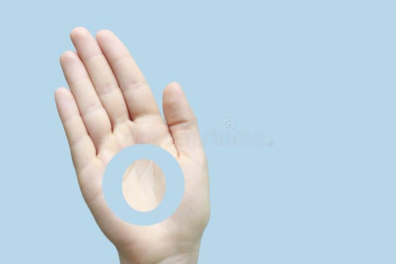 Cerchio blu, simbolo di diabete, sulla mano della donna, fondo blu, concetto di diabete immagini stock libere da diritti