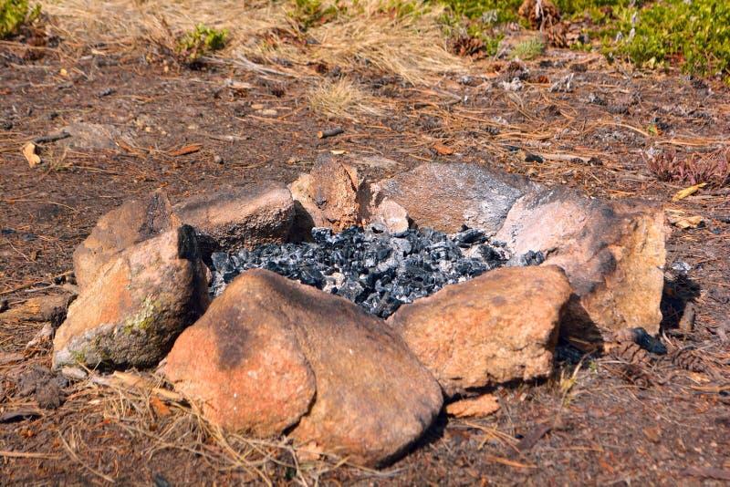 Cerchio della roccia del fuoco del campo con la cenere ed il legno bruciato fotografia stock libera da diritti