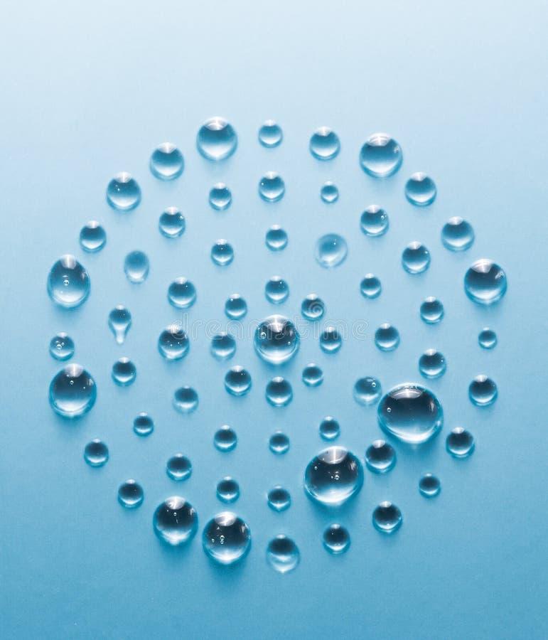 Cerchio delle gocce di acqua su un blu sottragga la priorità bassa immagini stock