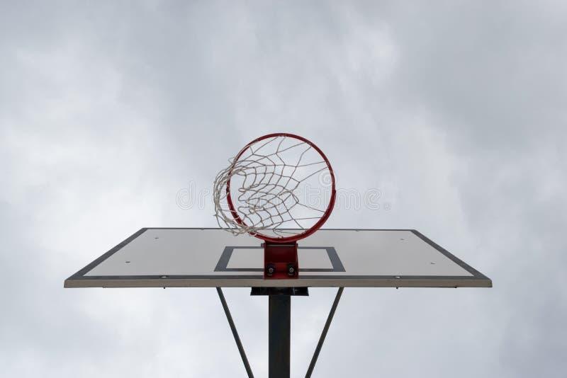 Cerchio di pallacanestro, canestro contro il cielo nuvoloso bianco Fuori, campo da pallacanestro della via immagine stock