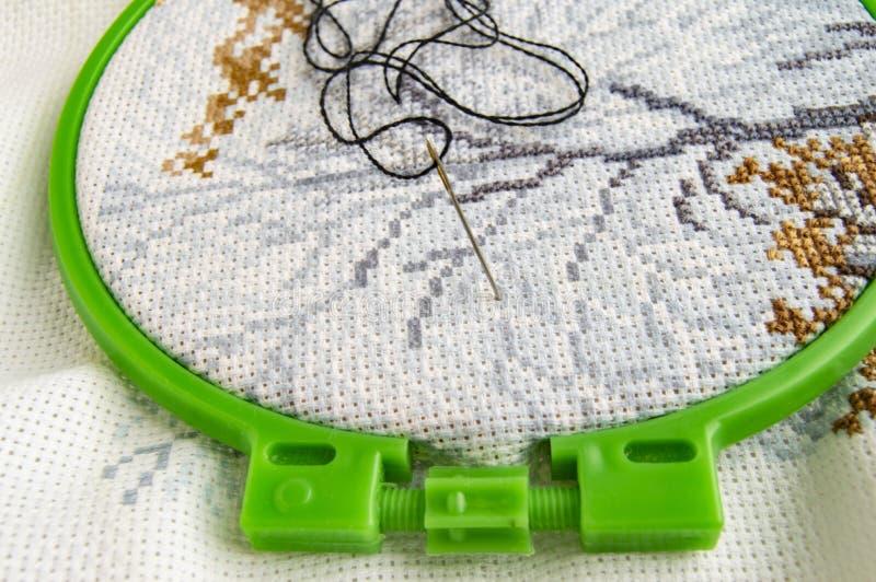 Cerchio di ricamo posto piano con tela ed il filato cucirino e l'ago di ricamo luminosi fotografia stock libera da diritti