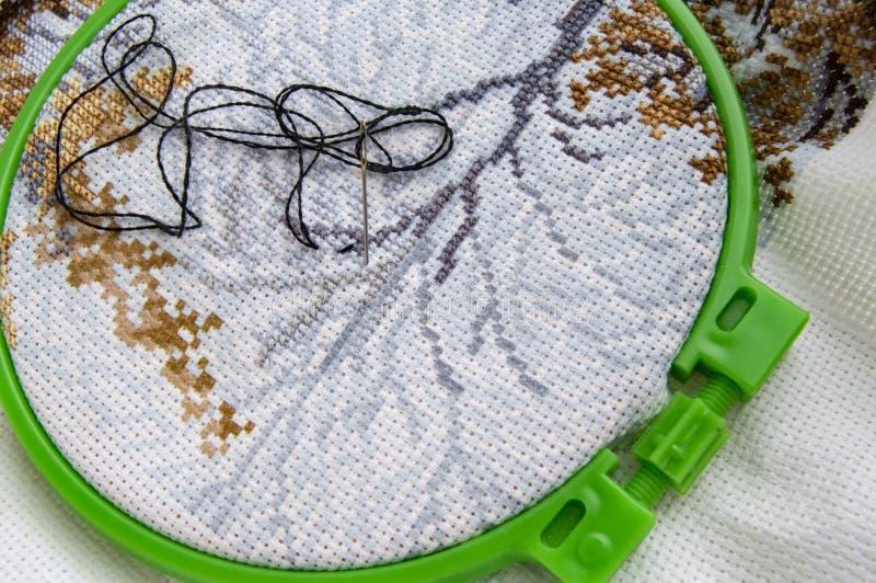 Cerchio di ricamo posto piano con tela ed il filato cucirino e l'ago di ricamo luminosi immagini stock