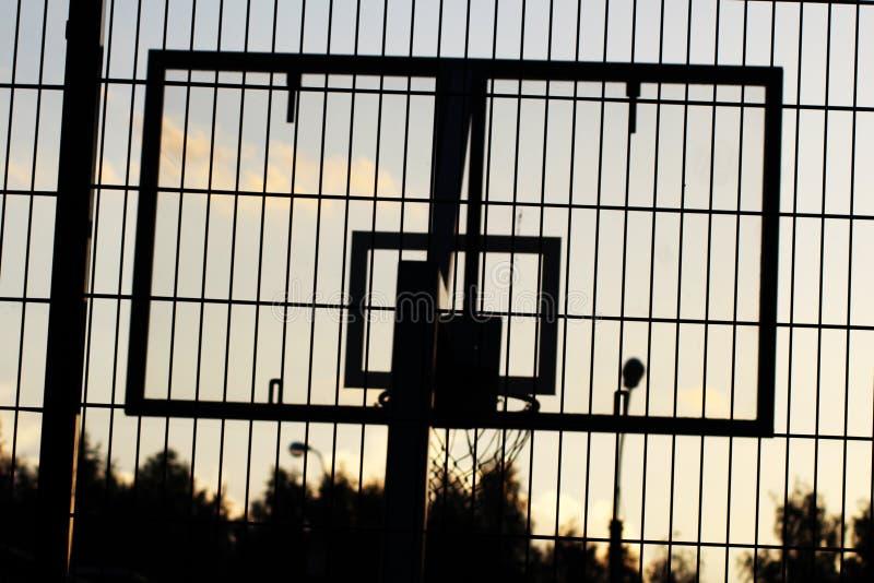 Cercle de basket-ball extérieur en silhouette de coucher du soleil photos stock